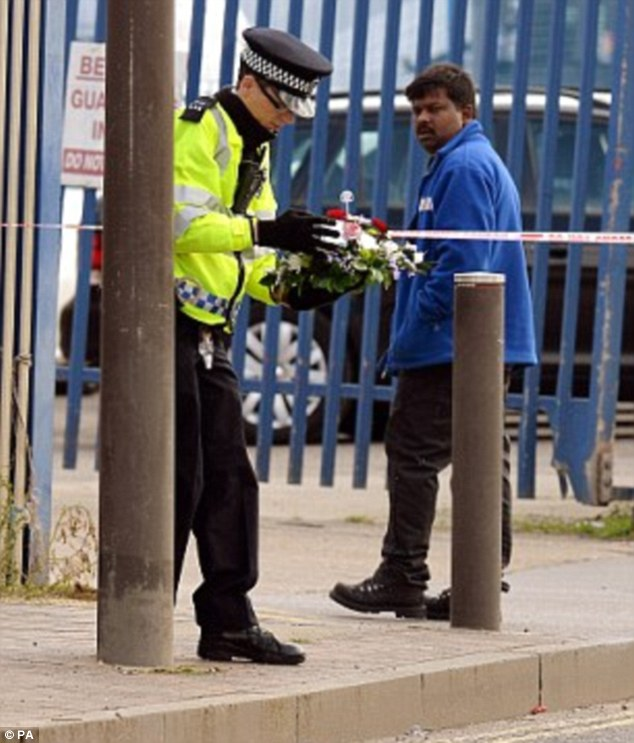 Flowers: A police officer places a tribute for the businessman at the scene