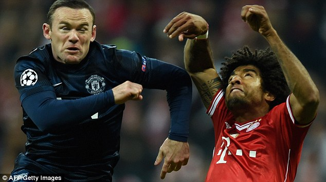 Eyes wide shut: Rooney and Dante (right) jump for the same ball during the first half