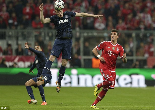 Focus: Phil Jones keeps his eye on the ball to stave off the threat of Mario Mandzukic