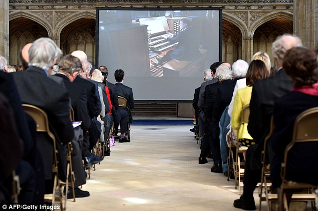 Guests watch a screen showing British concert organist Thomas Trotter giving a recital