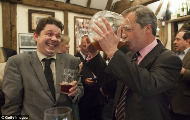 Mr Farage drinks beer from a large glass at the Bolton Arms pub after speaking at a Ukip public meeting at Old Basing Village Hall