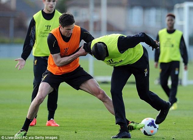 Tussle: Martin Kelly (left) tackles Mamadou Sakho at Melwood