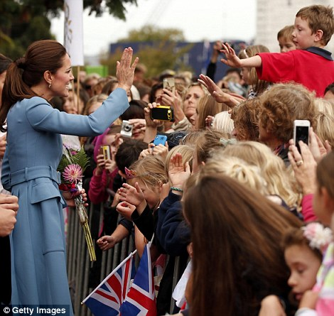 Kate waved to a young boy who had been lifted onto his parent's shoulders