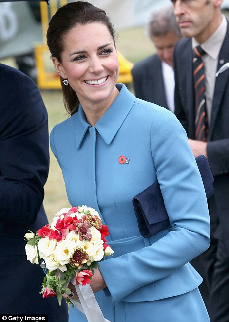 The Duchess waved as she held a bouquet of red and white flower