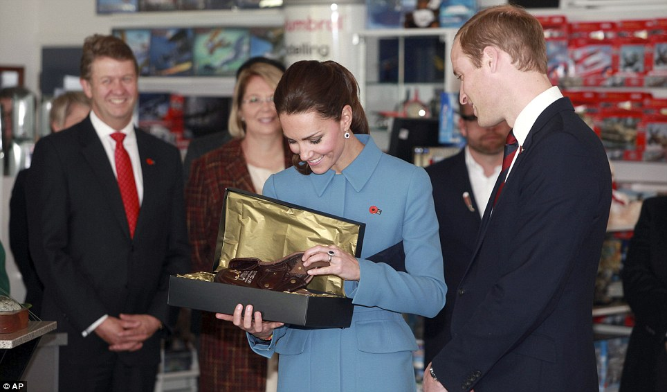 Gift for George: Kate and William look at a child-sized flying helmet, lined with possum skin, given to them by the museum as a gift for Prince George