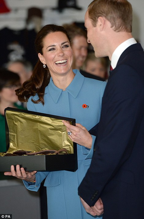 Delighted with the gift, Kate turns to William and laughs