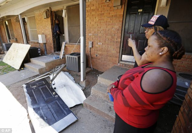 Raid: Residents look on as workers repair a neighbor's front door after agents broke it down Wednesday