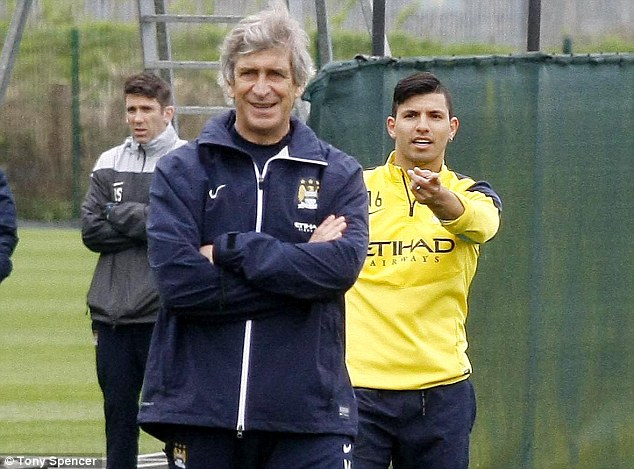 Meanwhile... Sergio Aguero (right) and Manuel Pellegrini pictured in Man City training on Friday