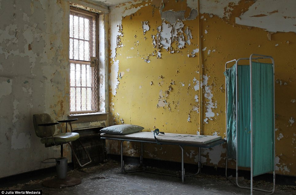 The doctor won't see you now: A therapy room lies abandoned with straps still trailing across the bed. The remains of the complex will be demolished within months