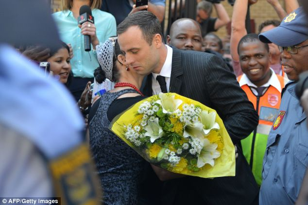 A woman hugs Oscar Pistorius after handing him flowers as he leaves court in Pretoria today during his ongoing murder trial. The athlete was today accused of shooting his girlfriend through a toilet door as the couple talked and argued in the early hours of Valentine's Day last year
