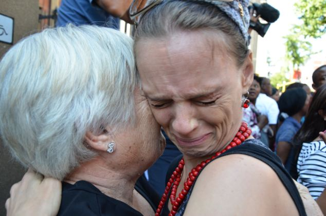 Oscar Pistorius' supporter Juanita (surname not provided) busts into tears after giving the athlete a bunch of flowers as he left the court