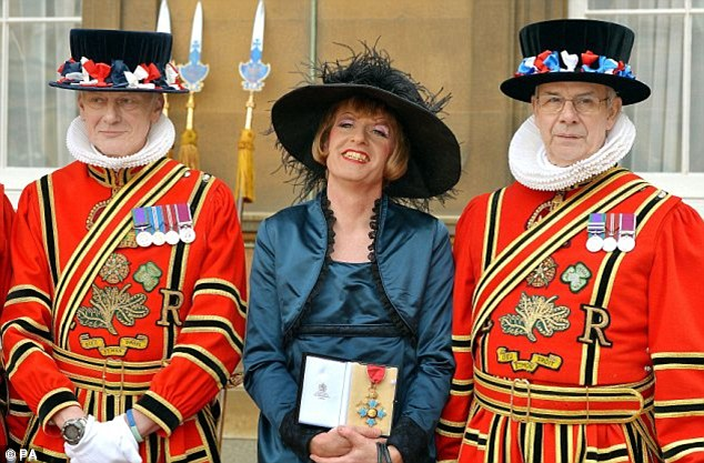 Grayson Perry pictured outside Buckingham Palace holding the CBE