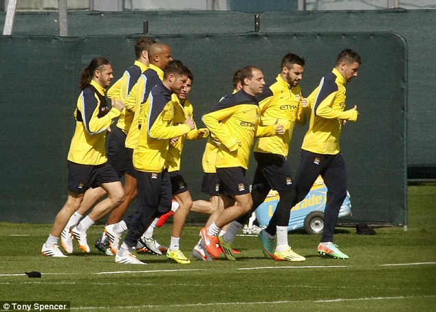 Warming up: City players jog around the pitch as they get the training session underway on Friday
