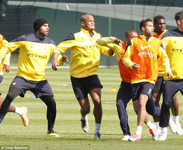 Focused: Joleon Lescott (left) and Vincent Kompany have their eye on the ball as a cross is swung in