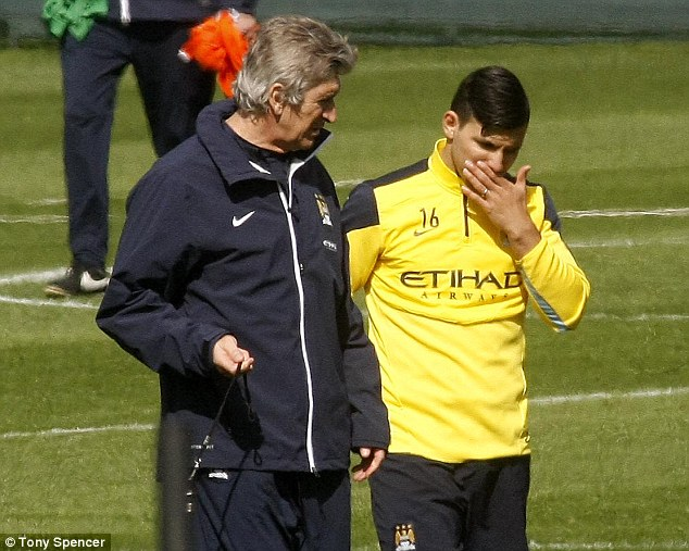 Chat: Manchester City manager Manuel Pellegrini has a few words with striker Aguero during training