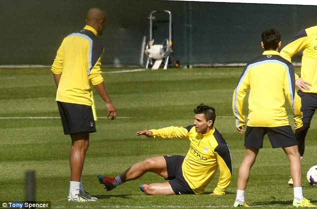 Going to ground: Aguero makes a slide tackle as he gets ready to return in Sunday's match