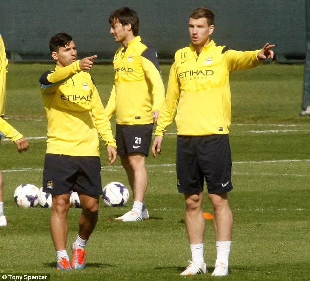 This way to the title: Aguero and Edin Dzeko (right) have a discussion during training on Friday