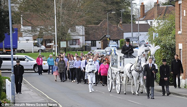Much-loved: People lined the streets of his Hampshire village or walked with his coffin on his final journey