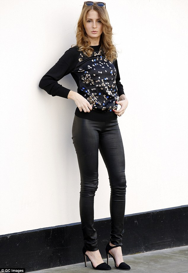 Rock chick: Millie finished her day by changing into an embellished jumper and skintight leather trousers