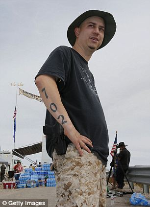 With a sidearm strapped to his side, Anthony Herrea stands along a protest area