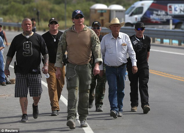 Brothers in arms: Rancher Cliven Bundy (2nd R) is escorted Friday by militia members in Bunkerville, Nevada