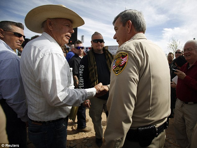 Deal: Cliven Bundy shakes hands with Sheiff Doug Gillespie on Saturday morning as the rancher comes to a deal to stop federal agents rounding up his cattle