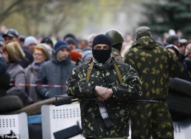 An armed man stands in front of a group of pro-Russian protestors near police headquarters in Slaviansk, a town around 90 miles from the border with Russia