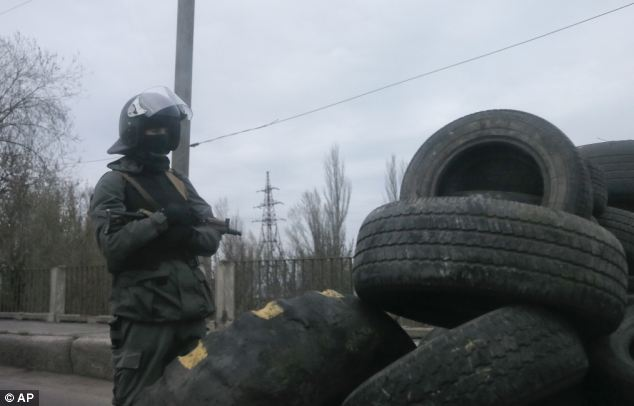 The checkpoint has been erected from used tyres and is manned by armed and masked protestors