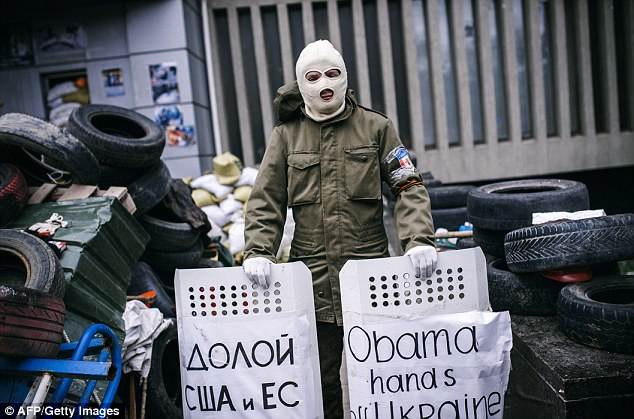 A masked protestor stands guard outside the headquarters of Ukraine's security agency in the eastern city of Lugansk. Separatists demanding a referendum to join Russia seized the building a week ago as a wave of secessionist anger swept eastern Ukraine