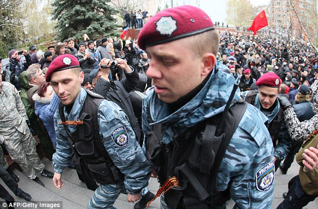 Members of the disbanded Ukraine's elite Berkut riot police, together with Russian separatists, enter the seized regional police headquarters in Donetsk today