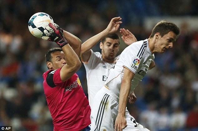 Holding on: Almeria's goalkeeper Esteban Suarez, left, vies for the ball with Real Madrid's Alvaro Morata, centre, and Llorente