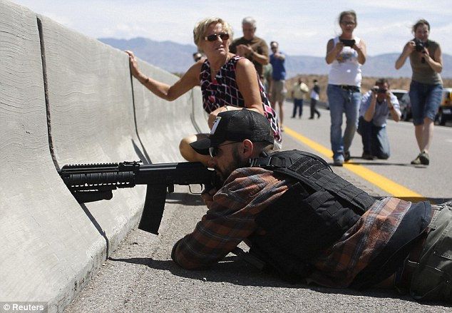Firepower: Protester Eric Parker from central Idaho aims his weapon from a bridge next to the Bureau of Land Management's base camp where seized cattle