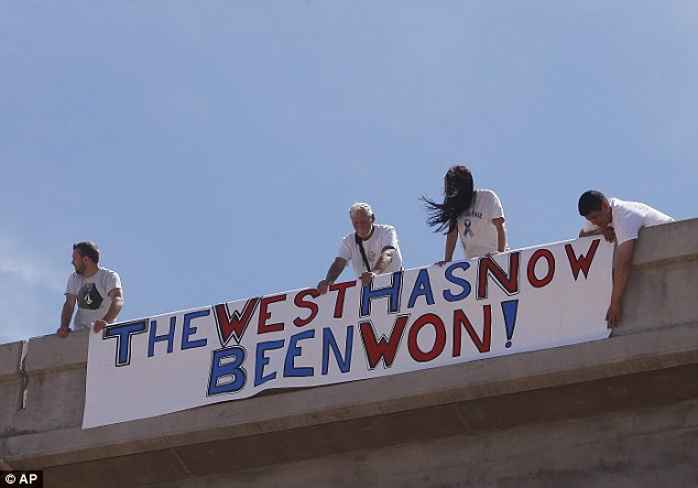 Mission accomplished: Supporters of the Bundy family hang a sign on the I-15 highway just outside of Bunkerville, Nevada