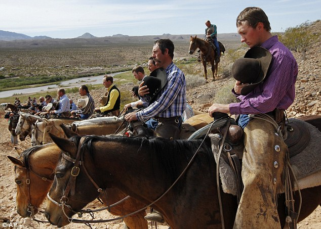 Cowboys and patriots: Kholten Gleave, right, of Utah, pauses for the National Anthem outside of Bunkerville , Nev. while gathering with other supporters of the Bundy family to challenge the Bureau of Land Management