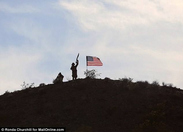 Armed militia members stand guard on a hilltop overlooking a Clive Bundy supporter camp near the Virgin River Saturday