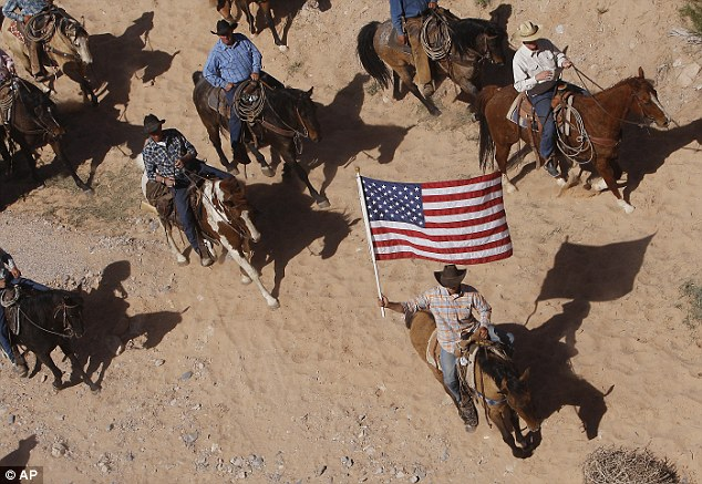 The Bundy family and their supporters fly the American flag as their cattle were released by the Bureau of Land Management back onto public land outside of Bunkerville, Nevada
