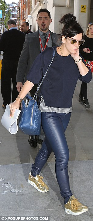 Leather love: Teaming dark blue leather jeans with a navy jumper, the singer kept warm by layering a striped top underneath her jumper as she went without a coat or jacket