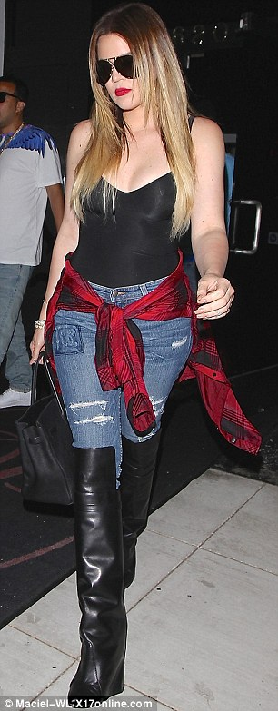Fancy footwear: The Keeping Up With the Kardashian star sported knee high wedge boots and deep red lipstick