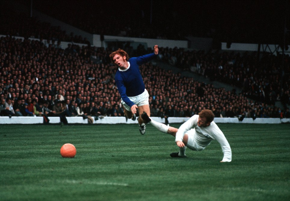 Billy Bremner (1942-1997), Leeds captain, brings down Everton's Alan Ball (1945-2007) with a foul challenge from behind as Leeds United played Everton at Elland Road, Leeds.