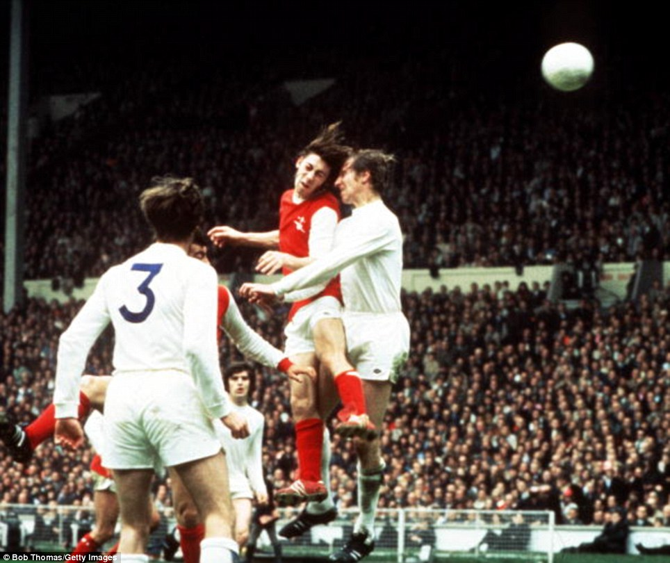 Arsenal's Charlie George jumps up to head a high ball under the challenge of Leeds United's Jack Charlton during the 1972 FA Cup final
