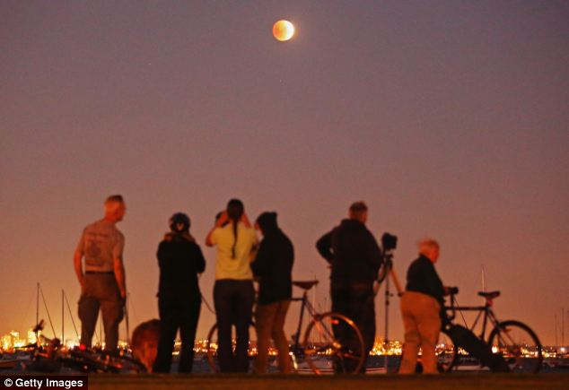 Taking in the view: Astronomers in North and South America are thought to be viewing the blood moon from 2.06 EST (7.06 GMT) to around 4.24 EST (9.24 GMT). Here, people watch the 'blood moon' rising over the water in Melbourne, Australia