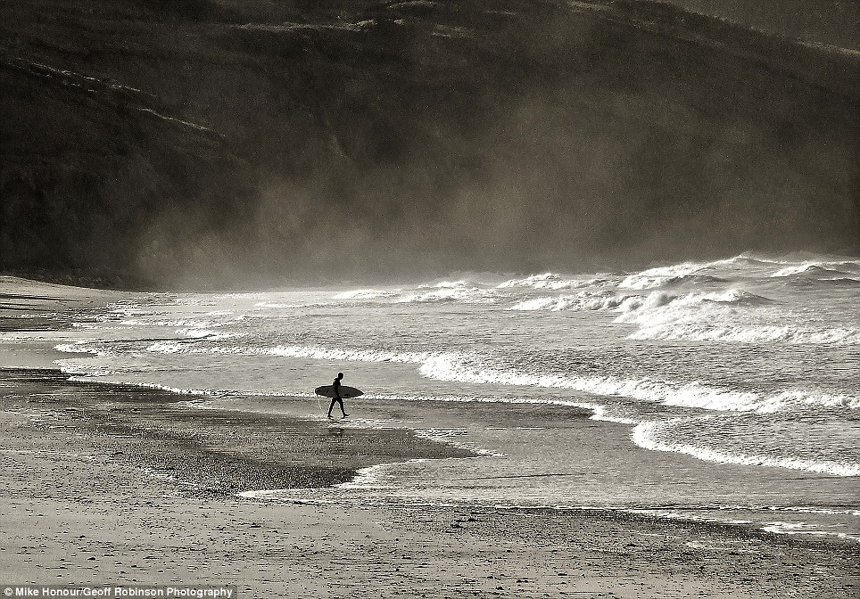 Heading out: A surfer walking out into the steamy Cornish surf at Praa Sands is the subject of this atmospheric photograph by Mike Honour