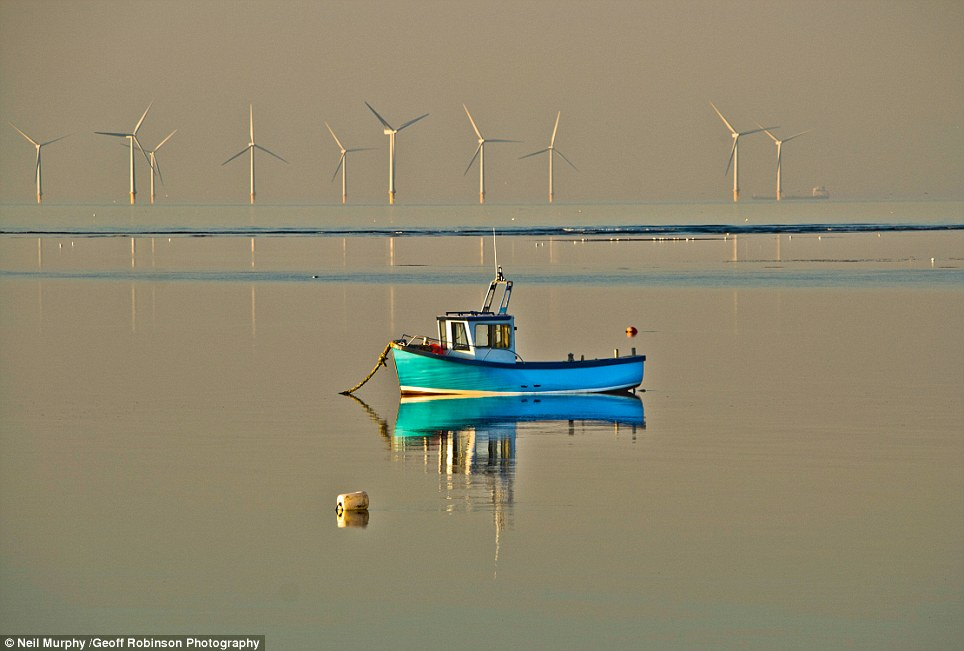 Modern landscape: A wind farm and tanker provide a contrasting backdrop for a traditional fishing boat at Meols on Merseyside, in this photo by Neil Murphy