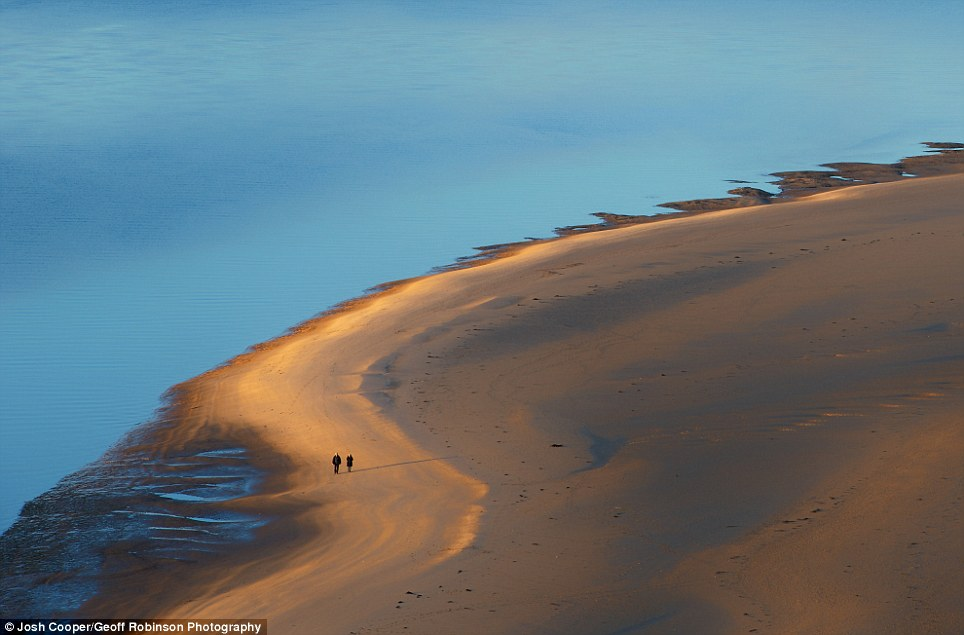 On the shortlist: This tranquil scene showing an elderly couple walking along the golden sand was photographed by Josh Cooper at Aberdovey in Wales
