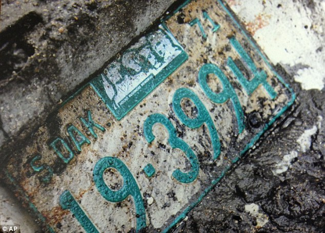 License: The license plate from the 1960 Studebaker was also unearthed in September 2013. The car remained hidden until last fall when a drought brought their it into view, authorities said