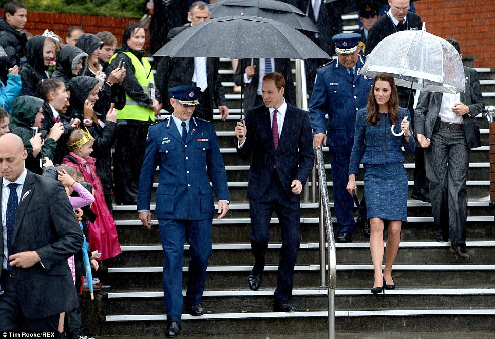 Sight for sore eyes: Despite the rain the waiting crowds clapped, cheered and took photos as the couple arrived