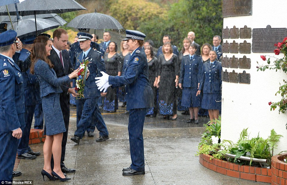 Getting wet: A police offer got caught in the downpour as the Royal couple lay a wreath in honour of officers killed on duty