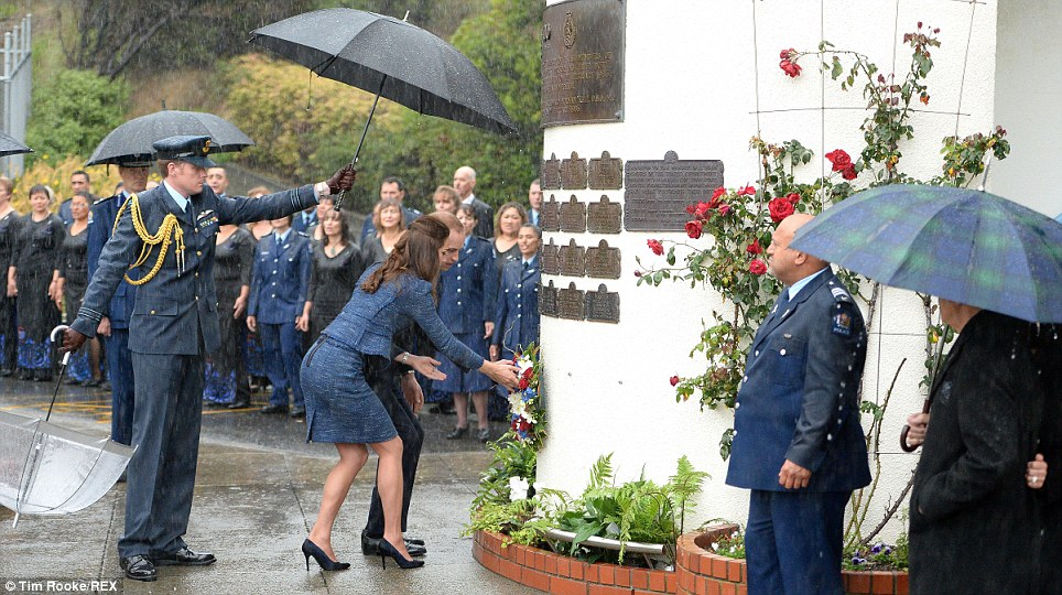 Staying dry: The Cambridges are sheltered by an umbrella as they lay the wreath