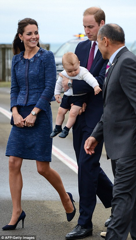 Curious: Baby George took in his surroundings as he was carried to the plane in the arms of William