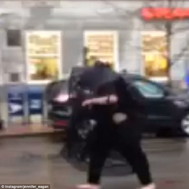 The suspect: Witnesses spotted the first bag being dropped off by a barefoot man dressed in all black with a black veil who was 'acting strangely' and yelling 'Boston Strong!'. Pictured above in an Instagram video leaving the scene
